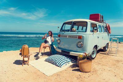 Vrouw op het strand bij een oldtimer met een oldtimerverzekering